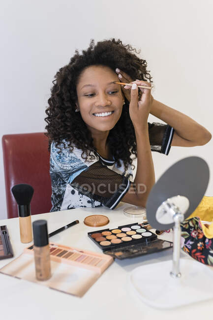 Smiling female make-up artist brushing eyebrows in studio — Stock Photo