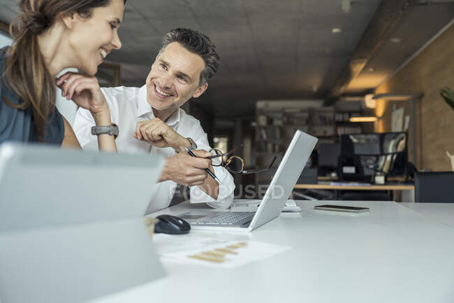 Male and female colleagues smiling while discussing over laptop at workplace — Stock Photo