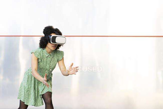 Jeune femme jouant tout en portant casque de réalité virtuelle contre le mur — Photo de stock