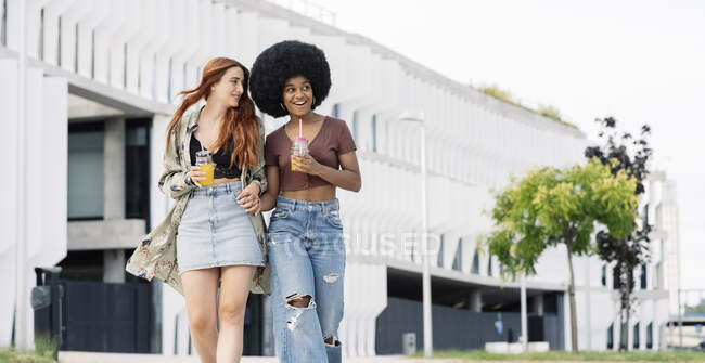 Здивований африканська жінка, яка тримається за руки своєї подруги, коли ходить містом. — стокове фото
