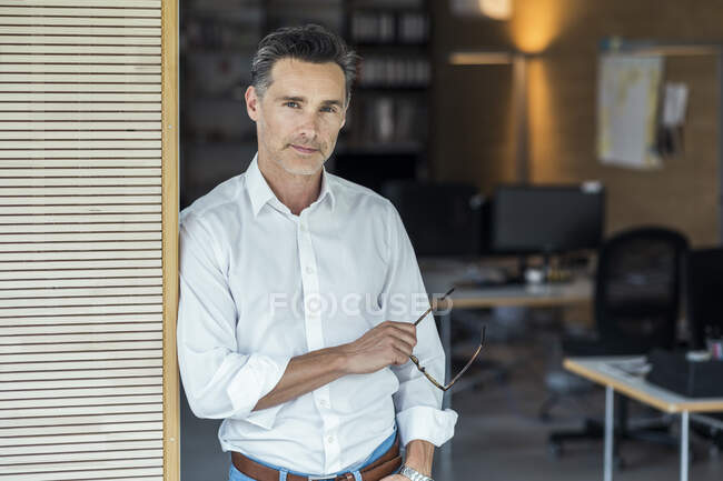 Businessman holding eyeglasses while standing at office doorway — Stock Photo