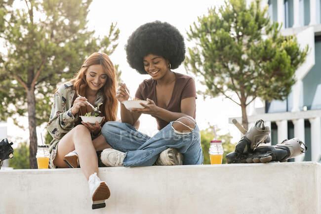 Щасливі друзі, які їдять їжу, сидячи на лавці. — стокове фото