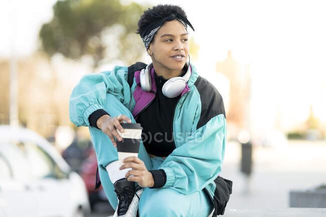 Femme tenant tasse réutilisable tout en regardant loin dans la ville — Photo de stock
