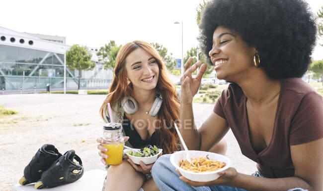Щаслива багатоетнічна дівчина розмовляє під час їжі. — стокове фото