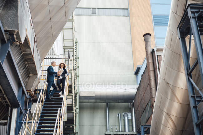 Professional team using digital tablet while standing on steps — Stock Photo