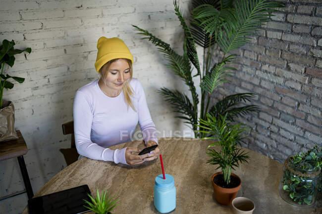 Молода жінка у жовтому капелюсі користується вдома розумним телефоном. — стокове фото