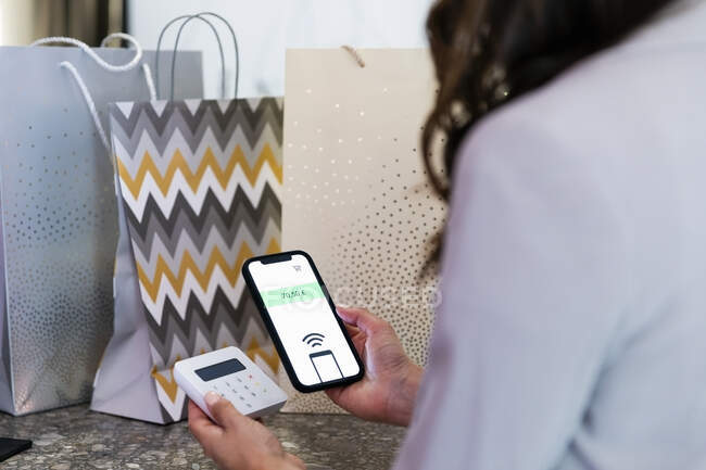 Woman holding smart phone while doing contactless payment in boutique — Stock Photo