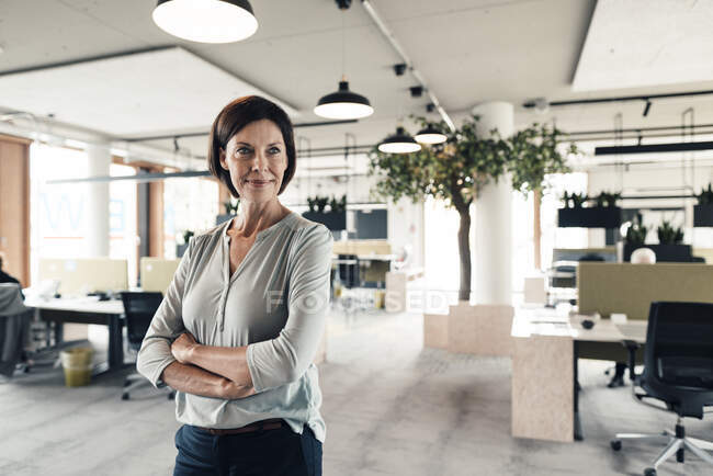 Confident businesswoman with arms crossed looking in office — Stock Photo