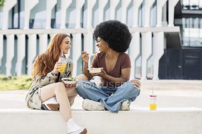 Друзі, які їдять їжу, сидять на лавці. — стокове фото