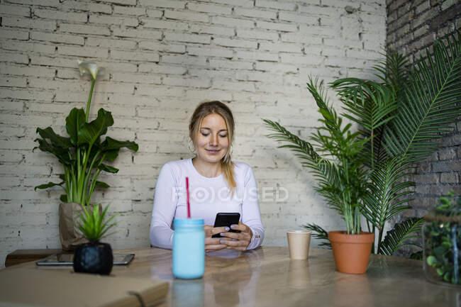 Молода жінка, за допомогою мобільного телефону, сидячи за столом у будинку — стокове фото