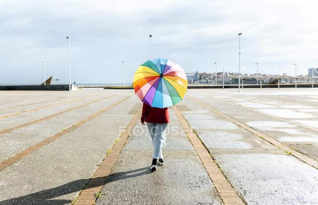 Femme marchant avec parapluie multicolore sur le sentier pendant la journée ensoleillée — Photo de stock