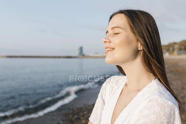 Jeune femme souriante avec les yeux fermés à la plage — Photo de stock