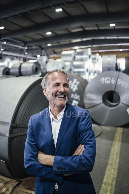 Gai professionnel masculin avec les bras croisés debout dans une aciérie — Photo de stock