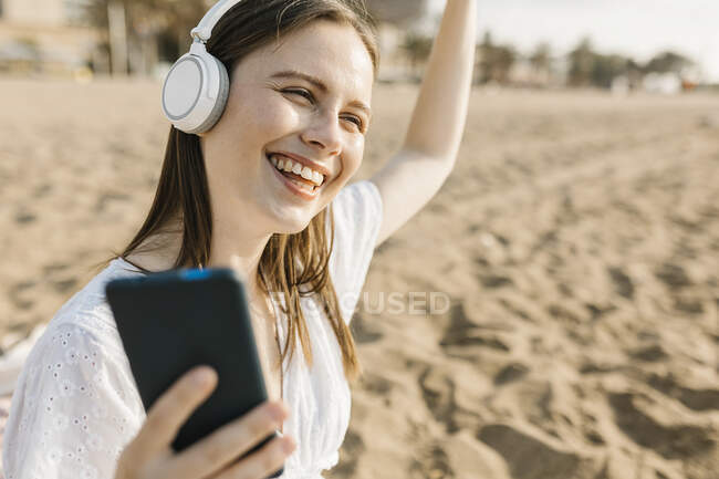 Femme heureuse tenant téléphone portable dansant tout en écoutant de la musique à travers des écouteurs à la plage — Photo de stock