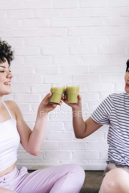 Amis toasting smoothie devant le mur de briques blanches — Photo de stock