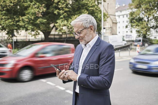 Homme d'affaires barbu utilisant un téléphone portable sur la route — Photo de stock