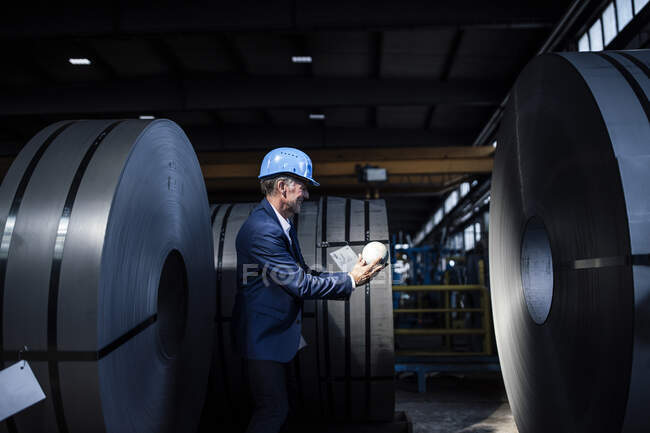 Homme d'affaires avec casque rigide tenant globe tout en se tenant à l'industrie sidérurgique — Photo de stock