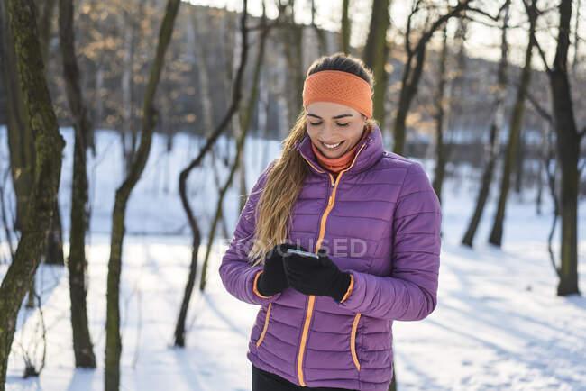 Femme en veste rembourrée utilisant un téléphone intelligent pendant l'hiver — Photo de stock