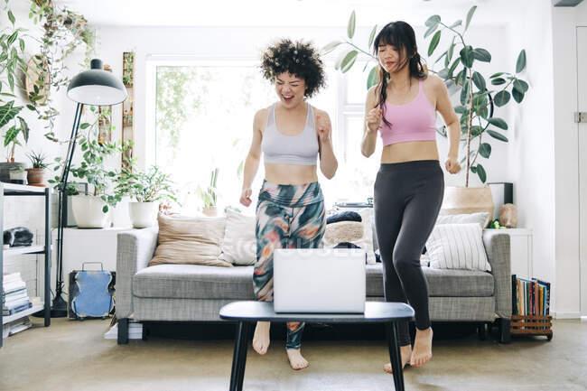 Des amis joyeux apprennent l'exercice grâce à un tutoriel en ligne sur ordinateur portable à la maison — Photo de stock