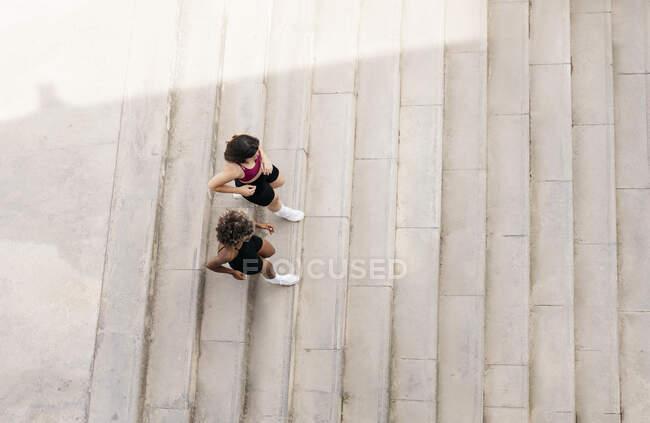 Amis femelles courant vers le bas sur l'escalier — Photo de stock