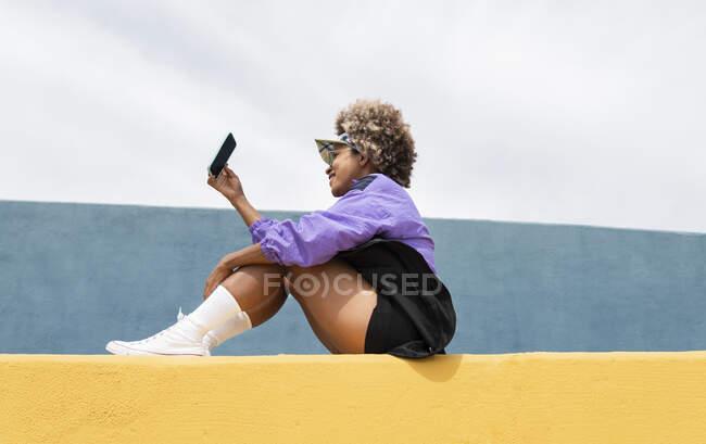 Femme adulte moyenne sur appel vidéo par téléphone mobile tout en étant assis sur le mur — Photo de stock
