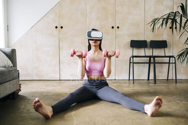 Femme utilisant casque de réalité virtuelle lors de l'exercice avec haltères à la maison — Photo de stock