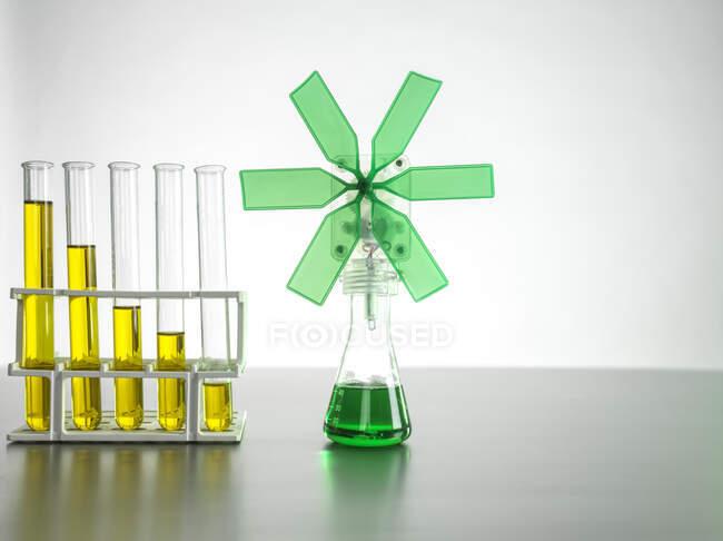 Зелена турбіна у склянці за допомогою тестових труб на столі. — стокове фото