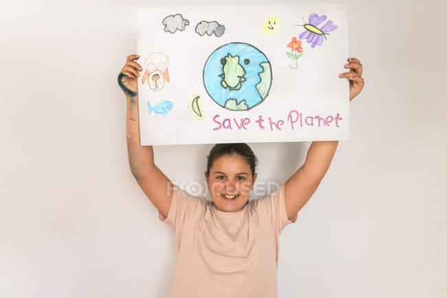 Fille souriante tenant affiche des questions environnementales à la maison — Photo de stock