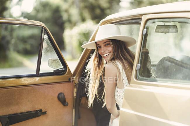 Souriant belle femme regardant par-dessus l'épaule tout en étant assis dans la voiture — Photo de stock