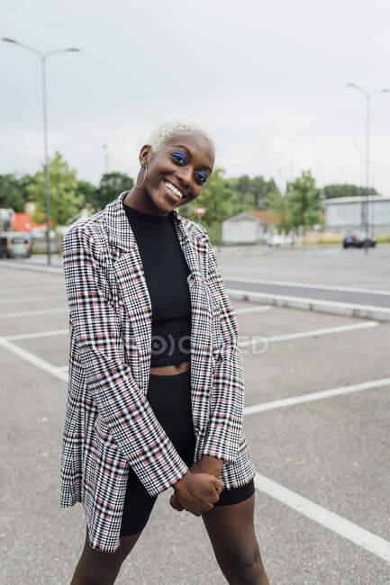 Jeune femme souriante debout sur la route — Photo de stock