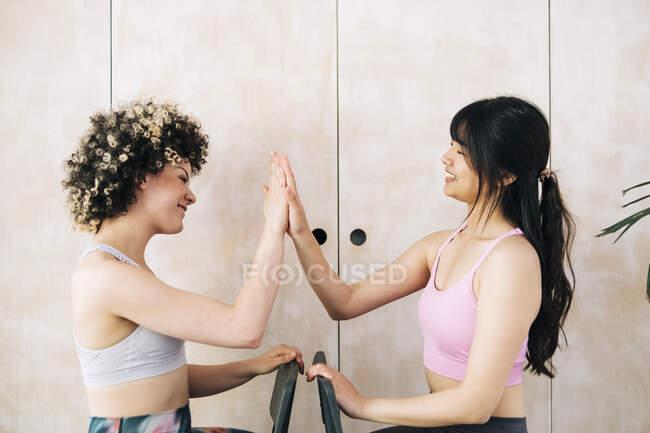 Amis féminins donnant high-five tout en étant assis à la maison — Photo de stock