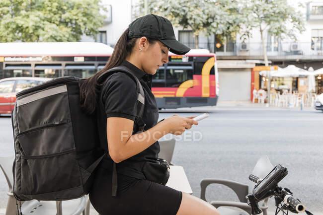Jeune accoucheuse utilisant un téléphone intelligent à vélo — Photo de stock