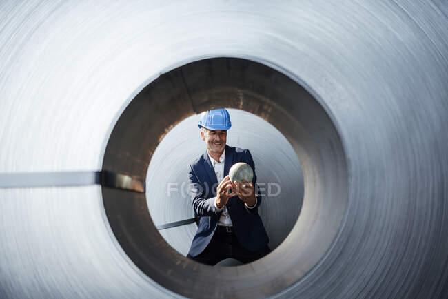Homme d'affaires souriant regardant le globe tout en s'appuyant sur un rouleau de tôle — Photo de stock