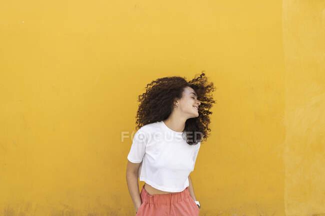 Femme jetant les cheveux devant le mur jaune — Photo de stock