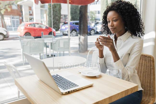 Femme d'affaires avec tasse de café en écoutant un appel vidéo via un ordinateur portable au café — Photo de stock