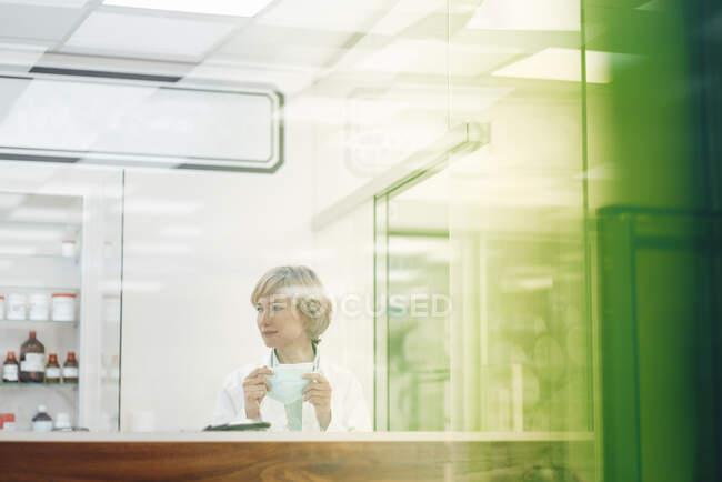 Pharmacienne tenant un masque facial au magasin médical — Photo de stock