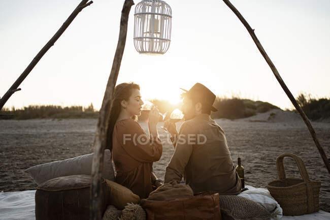 Couple boire du vin tout en étant assis à la plage au coucher du soleil — Photo de stock