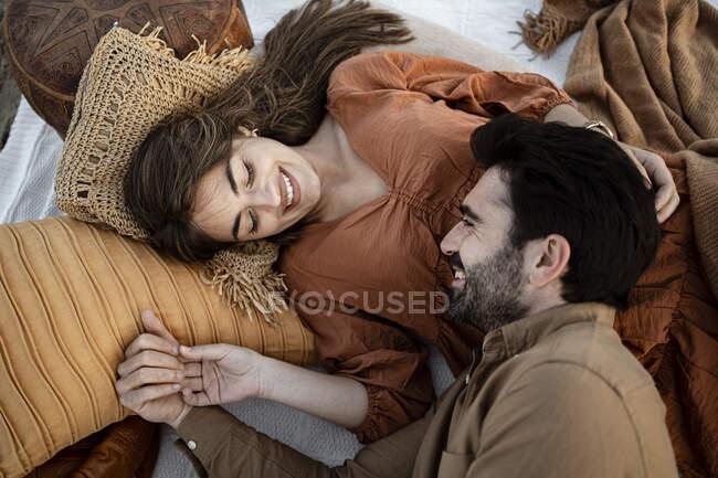 Couple souriant se regardant tout en se reposant sur une couverture de pique-nique — Photo de stock