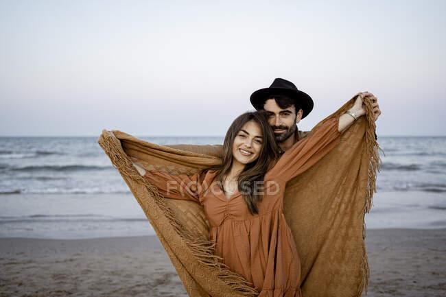 Petit ami debout derrière petite amie tenant couverture à la plage — Photo de stock