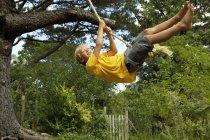 Garçon se balançant sur balançoire corde pendu à l'arbre dans le jardin — Photo de stock
