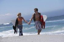 Giovani coppie che camminano lungo la spiaggia, trasporto tavole da surf sotto le armi durante il giorno — Foto stock
