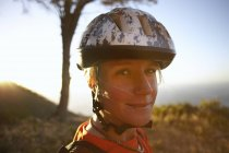 Female mountain biker wearing cycling helmet and smiling — Stock Photo