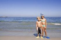 Мальчик и девочка, стоя бок о бок на песчаном пляже, носить трубки и ласты — стоковое фото