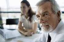 Focus on mature businessman in foreground, woman sitting at table in meeting room — Stock Photo
