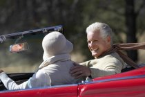 Side view of senior couple sitting in car and smiling — Stock Photo