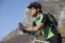 Male mountain biker sitting on bicycle, looking at view, holding water bottle — Stock Photo