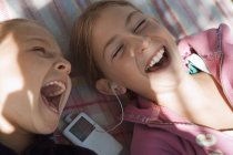 Two girls listening to MP3 player, sharing headphones — Stock Photo