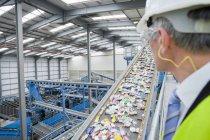 Uomo d'affari guardando plastica su nastro trasportatore — Foto stock