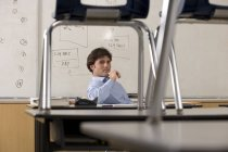 Enseignant de sexe masculin assis à un bureau dans la salle de classe, chaises sur un bureau — Photo de stock