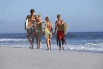 Две молодые пары, взявшись за руки во время ходьбы на пляже с доски для серфинга — стоковое фото